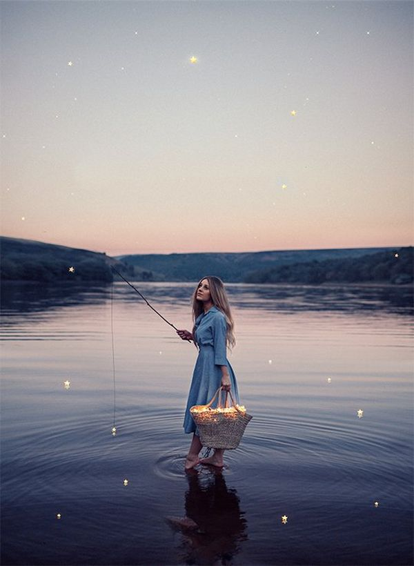 Rosie Hardy stands in a lake with a fishing rod, appearing to be fishing for glowing stars. Self-portrait by Rosie Hardy on a Canon EOS 5D Mark II.