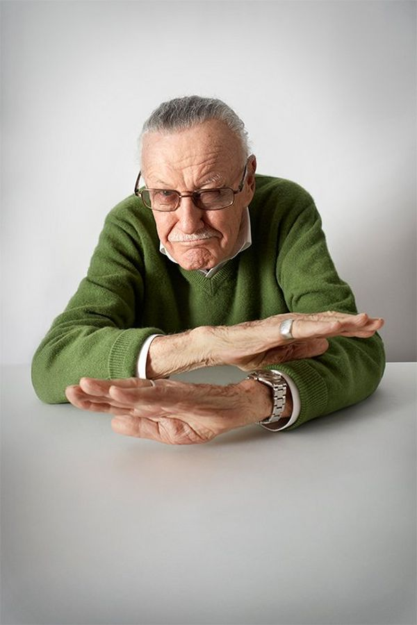 Stan Lee sits at a table gesturing with his hands as if telling a story. Portrait by Lorenzo Agius on a Canon EOS 5D Mark III.