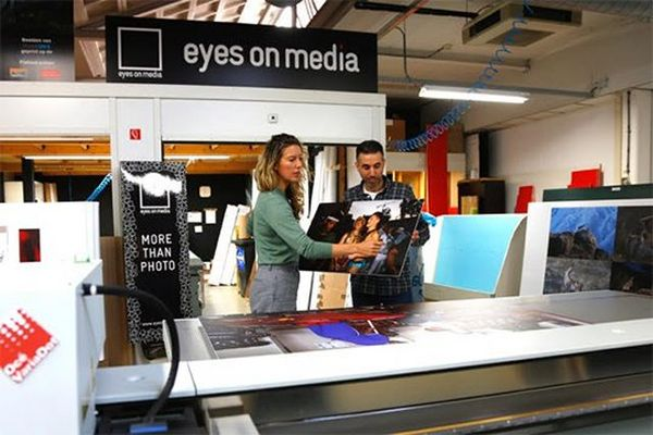 Ilvy Njiokiktjien lifts an exhibition print with a man at Eyes on Media printers.
