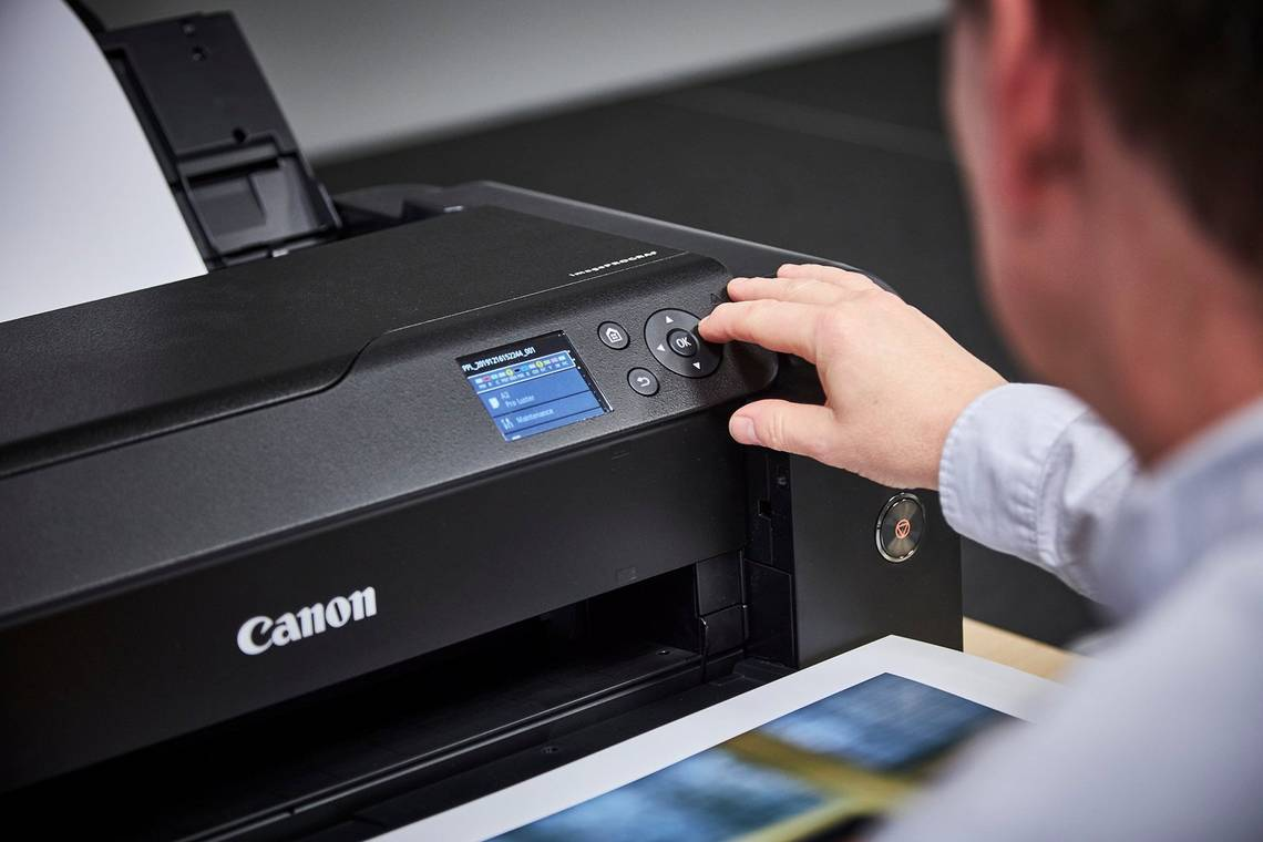 A man presses the buttons on a Canon PROGRAF printer to adjust the settings.