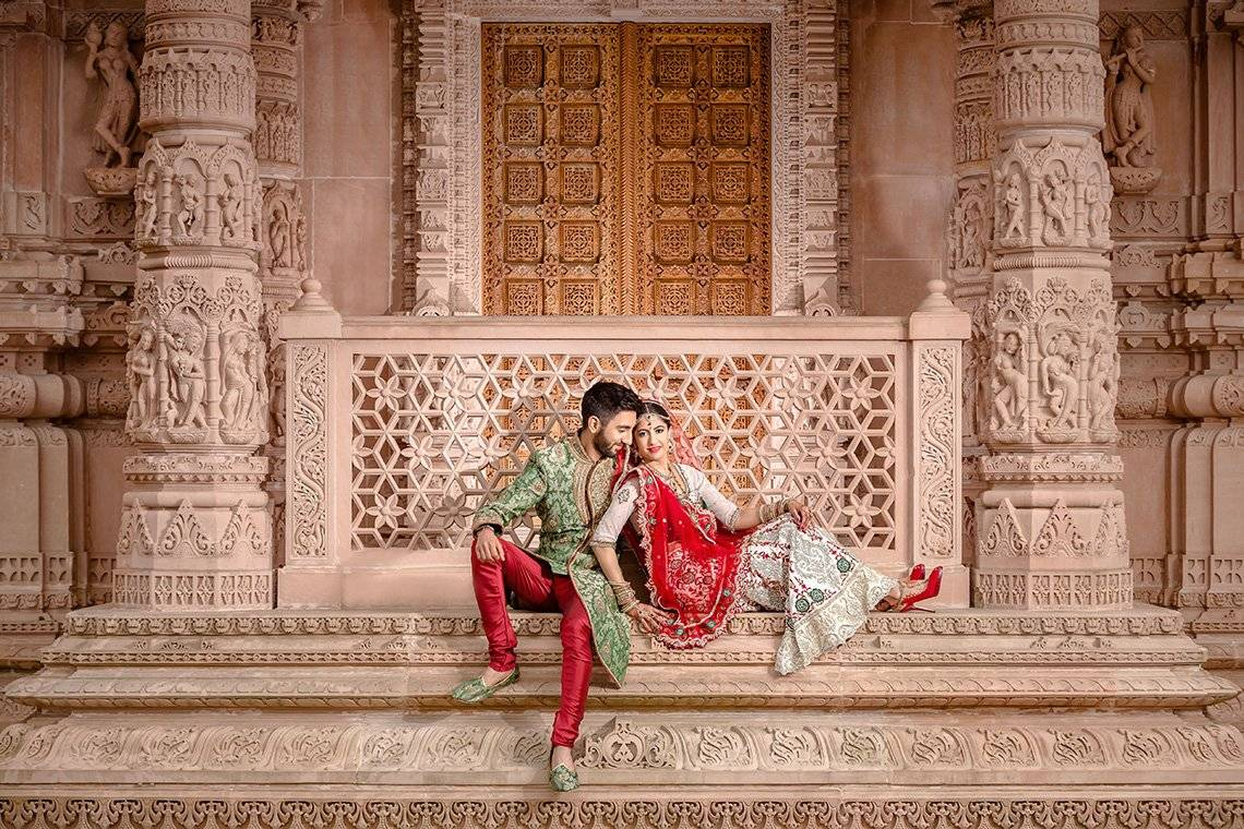 A newlywed couple sit outside the doors of a Hindu temple. Taken by wedding photographer Sanjay Jogia.