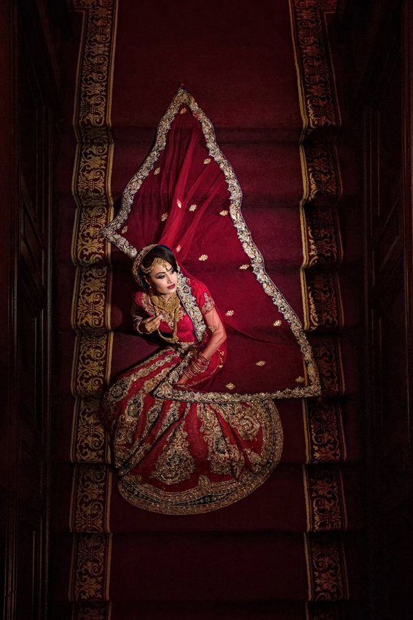 A bride sits on a red staircase, with her red veil laid out on the steps behind her. Taken by wedding photographer Sanjay Jogia.