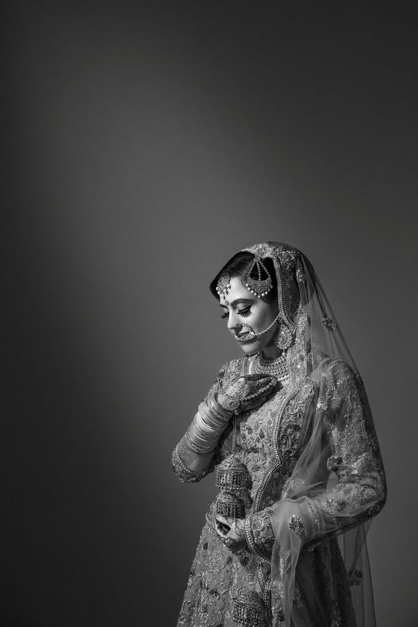 A black-and-white image of a bride adorned in jewellery and henna. Taken by wedding photographer Sanjay Jogia.