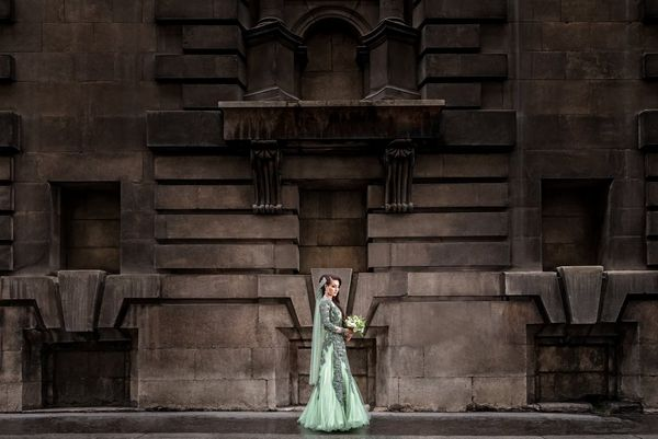 A bride in an intricately detailed mint green dress stands in front of the stone facade of a London building. Taken by wedding photographer Sanjay Jogia.