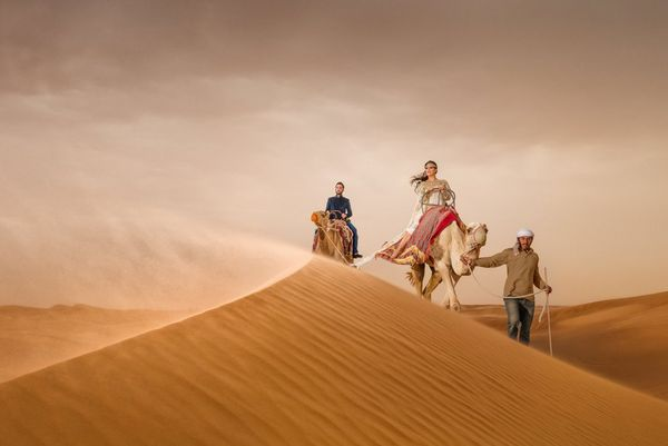A couple riding camels are led by a guide over sand dunes in Dubai. Taken by wedding photographer Sanjay Jogia.