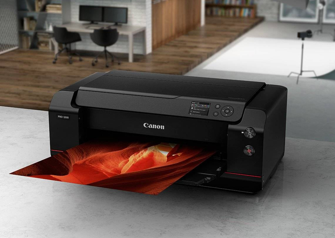 A Canon imagePROGRAF PRO-1000 A2 desktop printer on a marble-effect surface with a colourful red and orange print being output.
