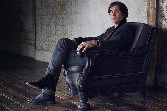 Irish actor Cillian Murphy, wearing a dark jacket and trousers, sits in a black armchair looking at the camera. Portrait by Lorenzo Agius.