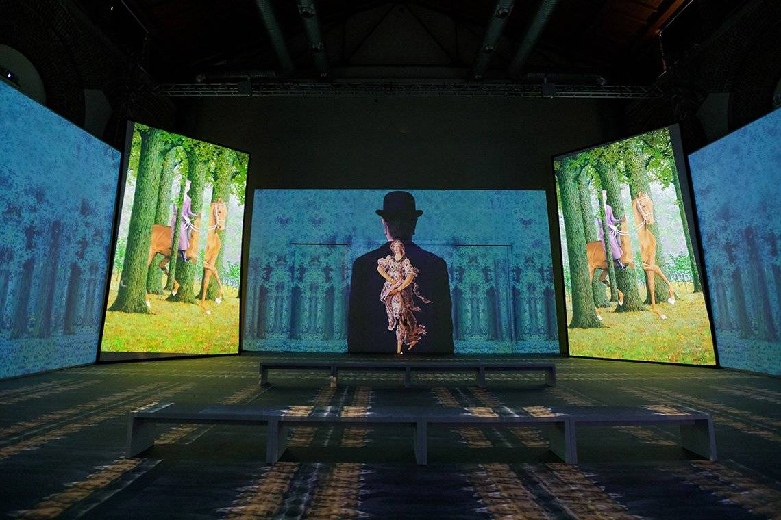René Magritte's famous works projected across a room in an immersive exhibit in Milan.