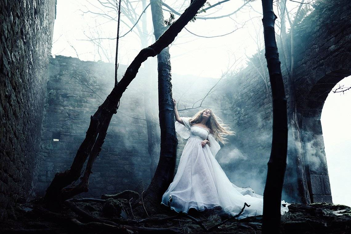 Rosie Hardy, wearing a flowing white dress, stands among three trees growing inside a roofless derelict room with smoke drifting around it.