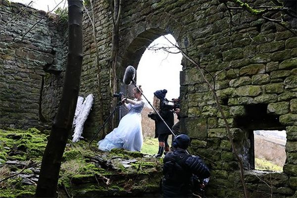 Helen Bartlett, wearing a flowing white dress, sets up her camera on a tripod in the arched doorway of a derelict building as other people wearing waterproof clothing look on.
