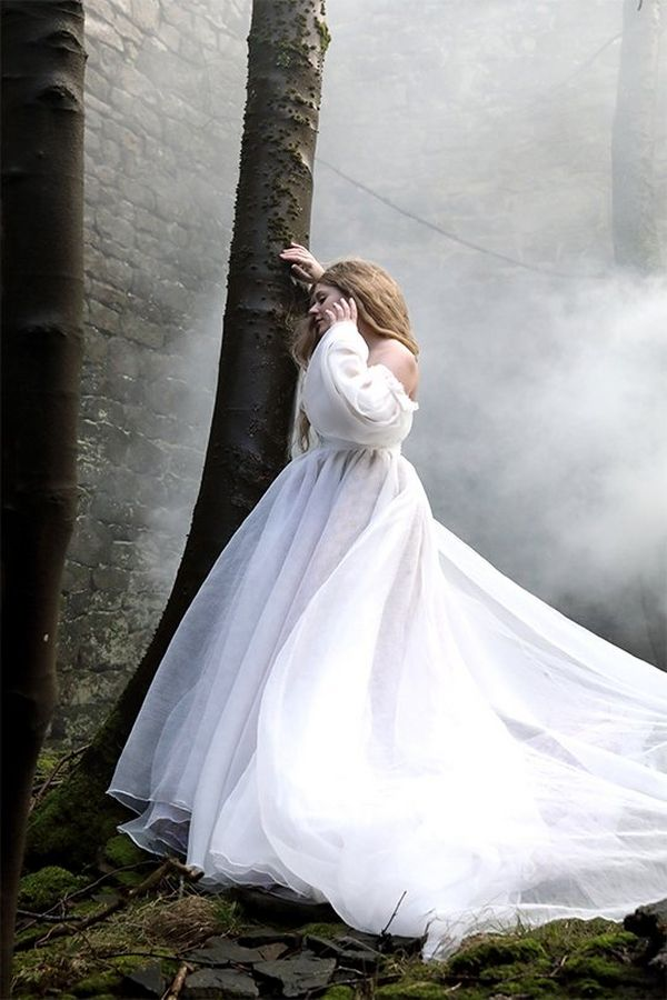 Rosie Hardy leans against a tree in a ruined cottage, wearing a flowing white dress and with mist behind her.