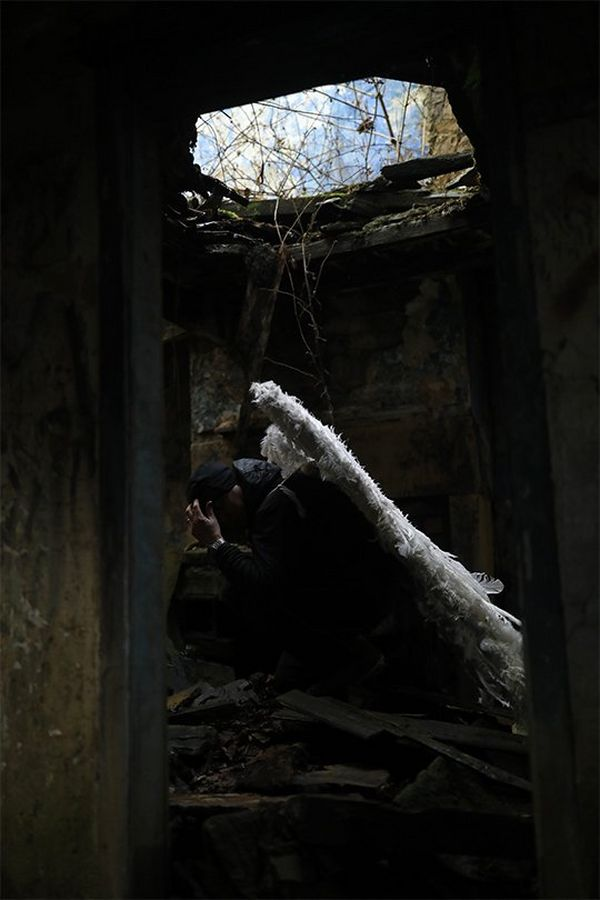Head in hands, wearing angel wings, Clive Booth squats inside a derelict room under a large hole in the roof.