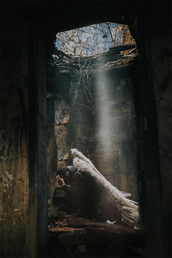 A ray of light shines through a hole in the roof onto Clive as he squats in a derelict room wearing angel wings.