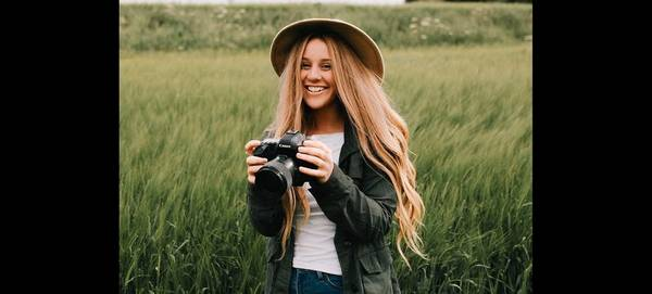 Rosie Hardy holds a Canon DSLR and smiles.