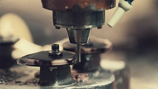 A close-up of a router shaping the eyepieces of a pair of glasses. A still from a video by Quentin Caffier.