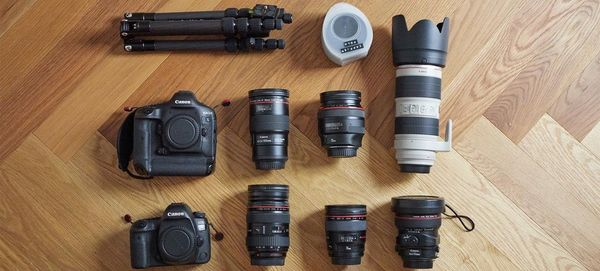 Quentin Caffier's photo kit on a wooden floor, including an EOS 5D Mark IV plus several lenses.
