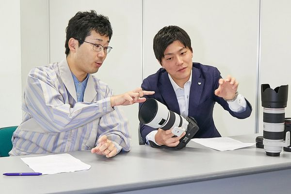 Mr Okuda points to the Canon RF 70-200mm F2.8L IS USM lens held by Mr Kawai as they sit at a table.