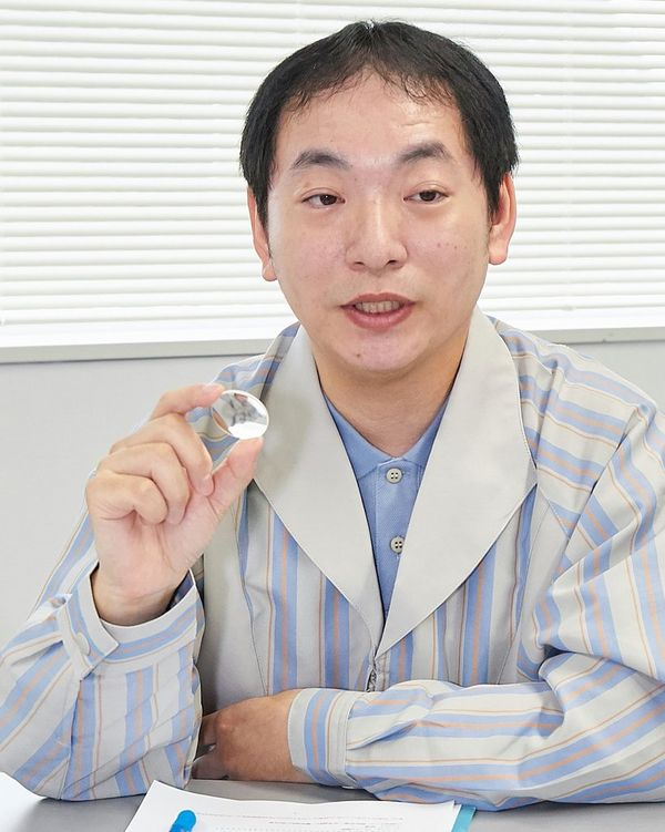 Canon Optical Design specialist Kenji Shinohara holds a UD aspherical lens between thumb and forefinger.
