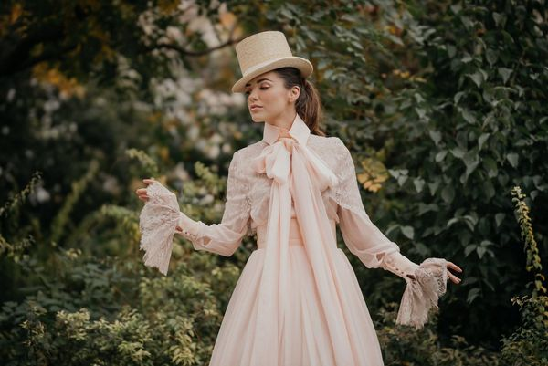 A model in a cream-coloured wedding dress and top hat poses in front of a blurred background of greenery.