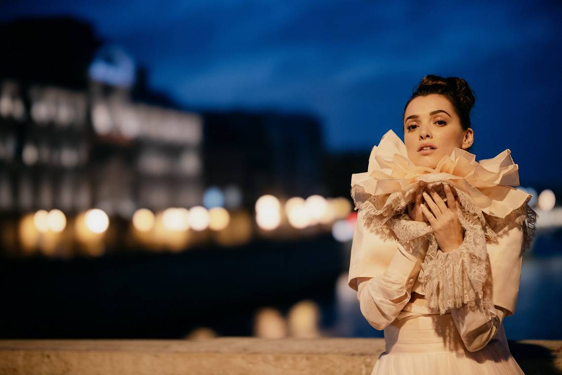 A night-time bridal portrait, with soft-edged bokeh on a row of lights in the background. Photography by Félicia Sisco.