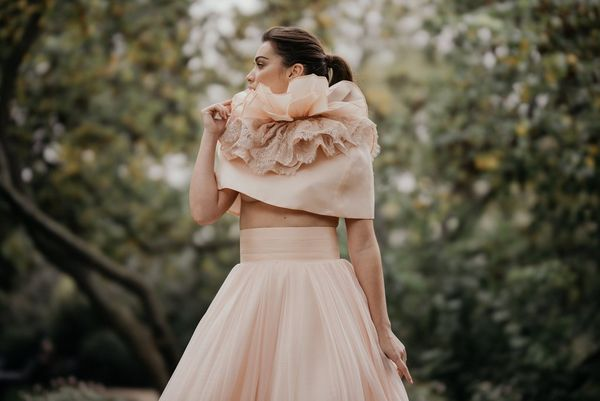 A model in a frilly wedding dress, photographed against a blurred background using the Canon RF 85mm F1.2L USM DS lens with Defocus Smoothing.