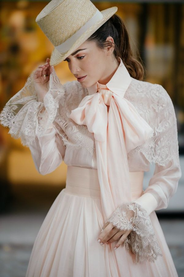 A model in a frilly wedding dress and top hat, photographed against a brightly-lit shop front in evening light.