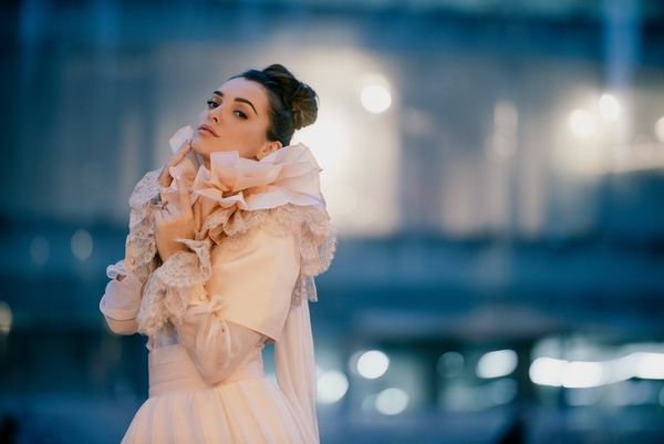 A model in a cream-coloured wedding dress, photographed in evening light against an out-of-focus background.