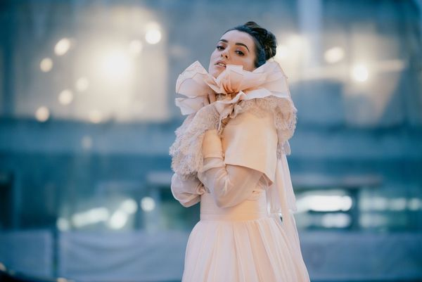 A model in a cream-coloured wedding dress against an out-of-focus background with creamier bokeh.