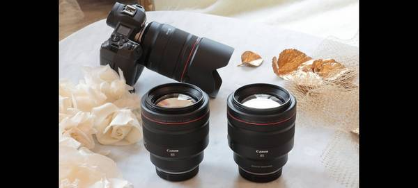 A Canon RF 85mm F1.2L USM lens and RF 85mm F1.2L USM DS lens side-by-side on a table, with a Canon EOS R behind.