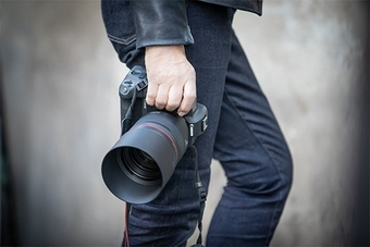 A photographer holds a Canon EOS R with an RF 85mm F1.2L USM lens.