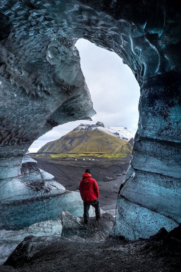 A man in a red padded coat stands at the mouth of an ice cave looking out at a bleak landscape with a snow-capped mountain in the distance.