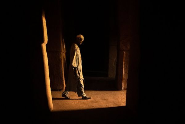 A man in flowing clothing and a cap walks barefoot through a dark room in Niger, the only light being from the doorway he's approaching.