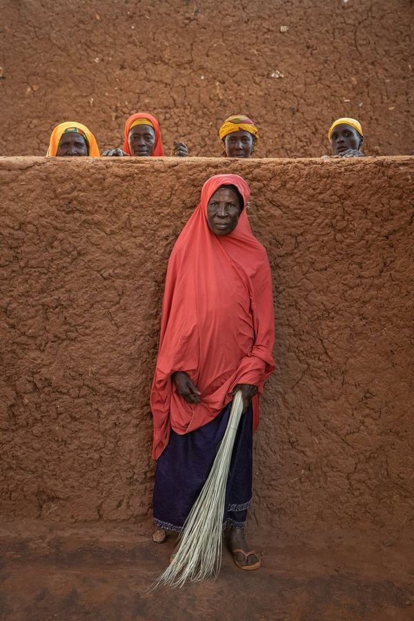 A woman stands with her back to a wall in Niger; four other women stand behind the wall, with just their heads visible. Taken by Joel Santos.