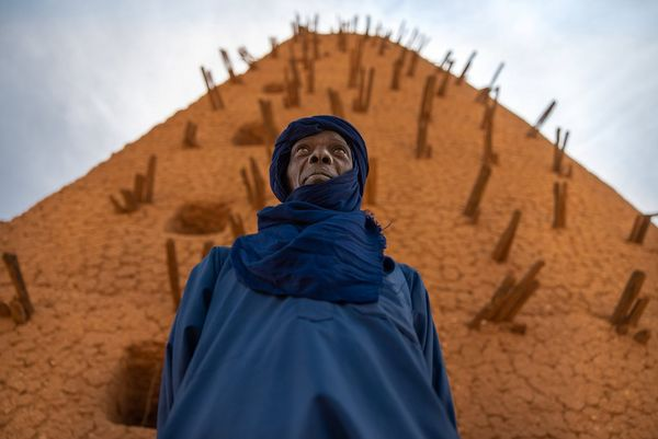 A man wearing an indigo robe and headscarf stands in front of a tower in Niger. Taken by Joel Santos.
