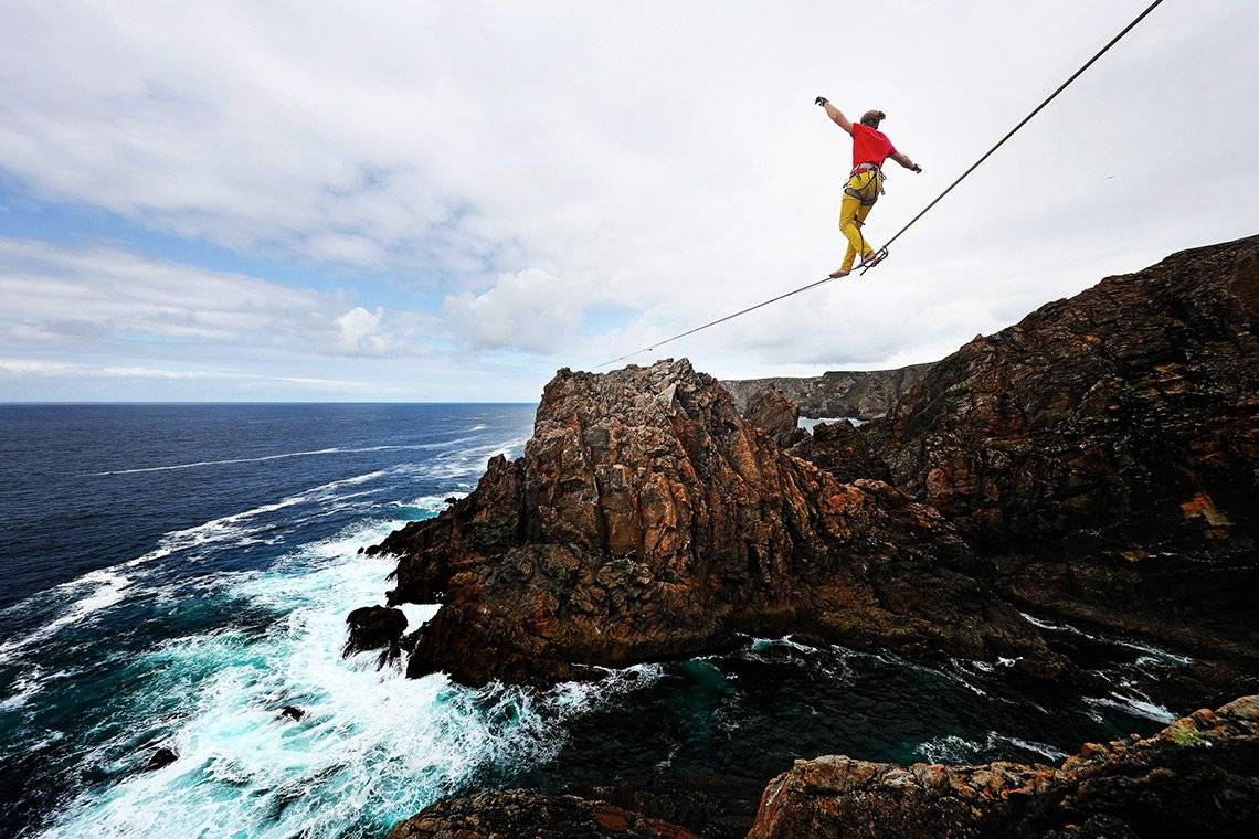 A man balances on a slackline suspended between two cliffs over the sea in Ireland.