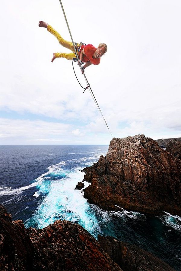 A slackliner balances on his hands on a rope over the sea, shot from below.