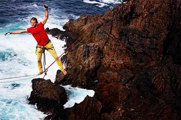 A man catches his balance on one foot, arms waving, standing on a rope suspended over the sea with the rocky shore visible below.