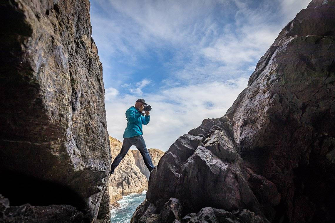 Action photographer Richard Walch shooting with a Canon EOS R, one leg on each side of a steep coastal cliff.