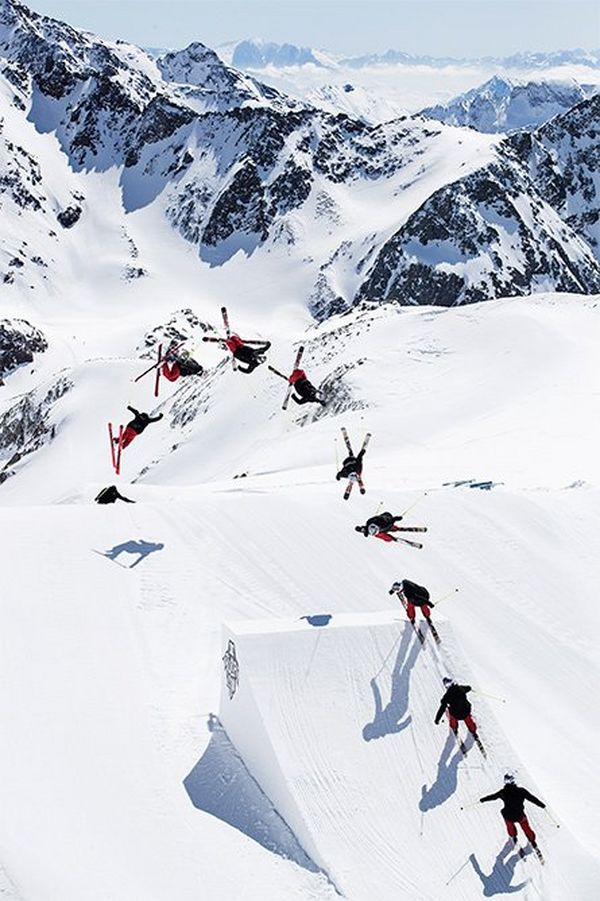 A multiple-exposure view of a skier executing a jump from a ramp, viewed from above.