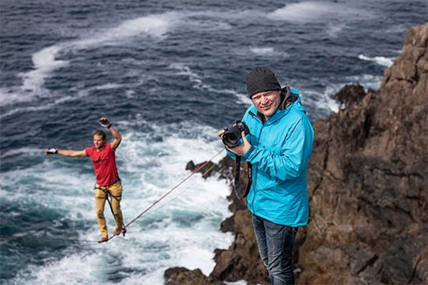 Photographer Richard Walch on a cliff holding a Canon EOS R, with a slackline walker on a line behind.