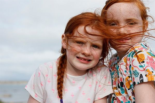 Two young red-haired girls by the sea, their hair blown by the wind.