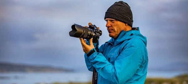 Richard Walch holds the Canon EOS R system on location by the sea.