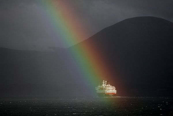 A striking rainbow illuminates a ship in an otherwise dimly-lit Norwegian fjord. Photo by Richard Walch.