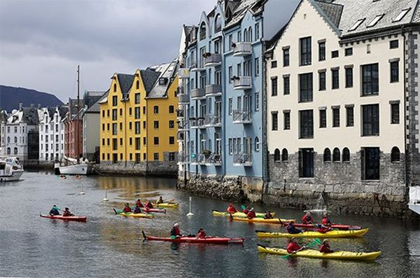 Kayakers on a river beside colourful houses, taken with a Canon RF 24-240mm F4-6.3 IS USM lens.