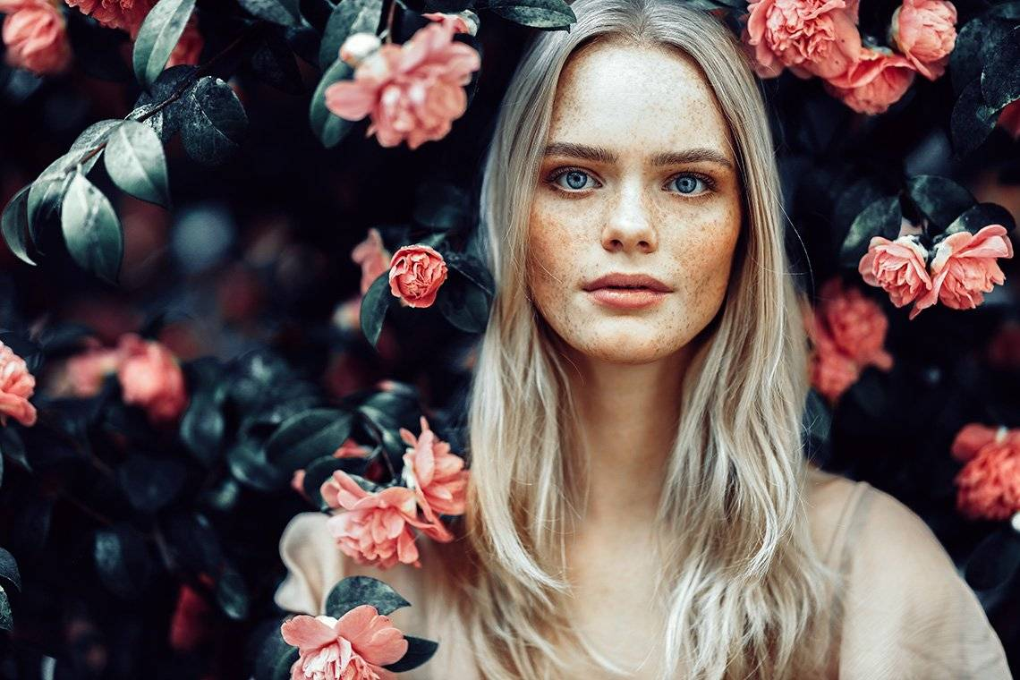 A blonde woman is surrounded by pink flowers and dark green leaves. Photo by Rosie Hardy with a Canon RF 85mm F1.2L USM lens.