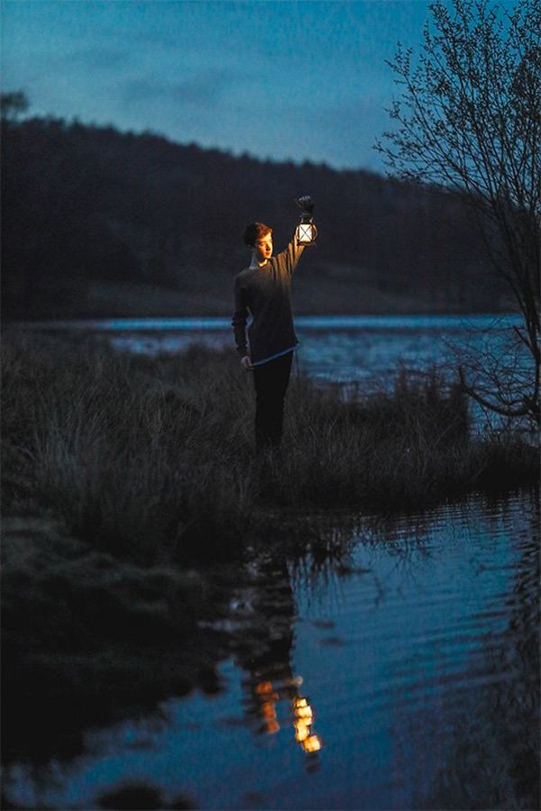 A boy holds a lantern by a lake at dusk. Photo by Rosie Hardy with a Canon RF 85mm F1.2L USM lens.