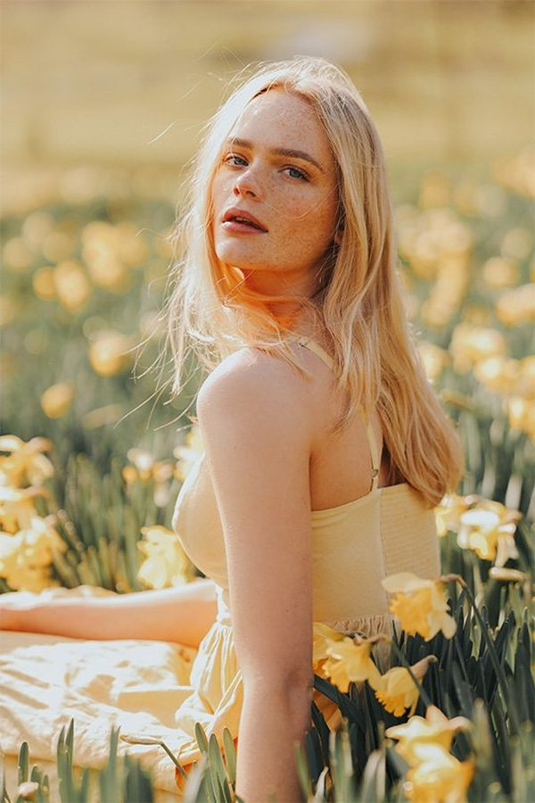 A blonde woman in a yellow dress sits in a sunny field full of daffodils. Photo by Rosie Hardy with a Canon RF 85mm F1.2L USM lens.