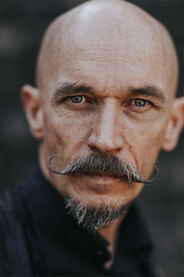 A close-up of a bald man with a styled, curled moustache. Photo by Rosie Hardy with a Canon RF 85mm F1.2L USM lens.