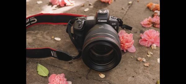Rosie Hardy's Canon EOS R with Canon RF 85mm F1.2L USM lens, with flowers beside it.