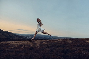Rosie Hardy leaps along a hill in the Peak District at sunset, wearing a white dress.